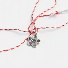 Mărțișor din argint delicat, în formă de floare cu cinci petale. După luna martie, mărțișorul poate fi purtat ca un charm la mână sau la gât, pe lanț sau șnur. Cu fir clasic alb-roșu și ambalat într-o punguță cadou, mărțișorul floare este gata pentru a fi oferit. #metaphora #martisor #martisoare #martisorargint #martisoareargint #martisordinargint #martisoaredinargint #silvercharm