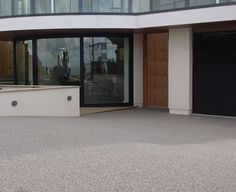 Clearstone Resin Bound Gravel. Silver grey granite bound in resin, complements steel and glass entrance to new build house in Whitstable, Kent