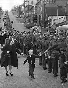 Canadian boy chasing after his father a member of the Canadian Army British Columbia Regiment who was on the march in New Westminster British Columbia Canada 1 October 1940.
