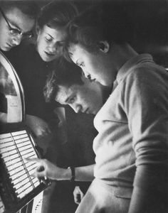 Teens selecting music on a jukebox (1950s)