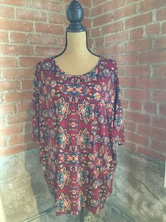 """LuLaRoe's Irma top is a loose, knit """"high-low"""" tunic with fitted mid-length sleeves. The extra length in the back makes it a great compliment to our leggings."""