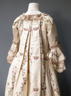 Back view, robe à la francaise, England (Spitalfield's), 1760s, remodeled 1780s. Ivory ground silk taffeta woven with a narrow self weave stripe, with gently curving flower and leaf meanders in puce, shaded tangerine flowerheads, red berries and sage green foliage, alternating with small sprays of flowers in deep rose pink and ivory. Trimmed with same tufted silks and corded wire loops.