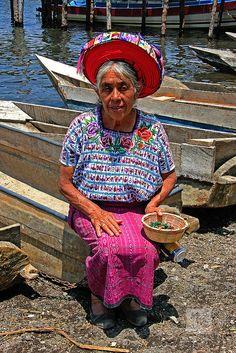 Mayan Lady in traditional dress sat on a boat, Santiago, Lake Atitlan, Guatemala