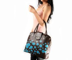 Fun illustration of colorful daisies stands up against a rich brown color leather. Its spacious interior  is perfect to carry all your daily must haves.  $165