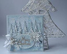 handmade Christmas card fromDorota_mk: Still freezers ... monochromatic pale blue ... lots of dimension ... rows of die cut fir trees popped up to form a fores ... die cut snowflake ane artificial berries in white frame the oval sentiment panel ... gorgeous card for display ...