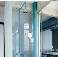 Aparentes, a tubulação do chuveiro e o cano de esgoto foram pintados de azul. O tom vibrante ganhou ainda mais força na presença da estrutura de concreto. Projeto do arquiteto Diogo Oliva.
