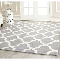 This contemporary wool rug features an ivory geometric pattern against a silver background. This wool rug is handmade from some of the softest wool fibers available. A durable canvas backing made of cotton ensures this rug will last a long time.