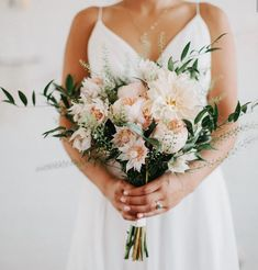 Loose bouquets of peachy blush Juliet garden roses, blushing bride protea, burgundy astrantia, burgundy sacbiosa, blush astilbe, blush nerines, sivler dollar eucalyptus, seeded eucalyptus, agonis, nagi, and plumosa wrapped in navy ribbon with the stems showing