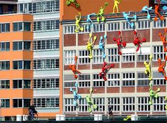 The Roggendorf House is covered by climbing figures called 'Flossis' by German artist Rosalie in Duesseldorf, Germany. (Martin Meissner/Associated Press)