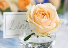 En enkelt rose er vakker sammen med bordkortet.