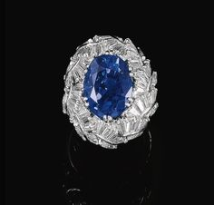SAPPHIRE AND DIAMOND RING, VAILLANT AND DUVERNE, CIRCA 1960 The oval sapphire weighing 12.74 carats, within a bombé surround of baguette, tapered baguette and marquise-shaped diamonds, French maker's marks.