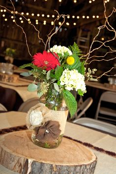 Reception:  high table decoration gallon -- wide-mouth mason jar with large natural burlap wrap decorated with a natural, chocolate and ivory burlap flower; flowers include Hydrangea, Gerber Daisy, Billy Balls and Corkscrew Willow branches with greenery