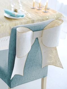 Bows on the back of chairs might be more feasible than covering them? At least less fabric
