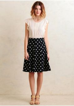 We adore this navy knee-length skirt designed with an adorable white polka dot print and a flared A-line silhouette. Complete with an elastic waistband for a defined silhouette, this lightly text...