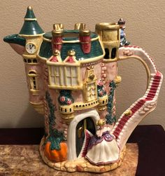 Vintage Cinderella Teapot by Fitz and Floyd. Hand painted and made in Sri Lanka in 1995. This gorgeous teapot shows Cinderella leaving the ball and losing her glass slipper on the staircase. Prince Charming is shown at the top of the staircase as he chases after her. The Fairy Godmother