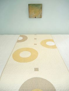 Can something be warm and cool at the same time? This runner is made with bold rings and squares in a restful palette. Soft mustard and linen tones on eggshell for the front with a complementing light khaki back and binding. Machine pieced and quilted. Hand finished binding. Machine