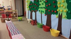 Apple orchard dramatic play. Mural on wall is made with felt. Ball pit balls with velcro stick to the trees. Provide baskets, wheelbarrow, step stools. The kids love this center!!