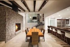 A large grey stone double-sided fireplace separates the dining room and kitchen from the living room. Large format marble sheets were used for the flooring in the main living and dining area.
