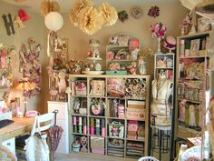 Love all the layers and colors in this studio. Really like the sewing pattern pom poms hanging from the ceiling.