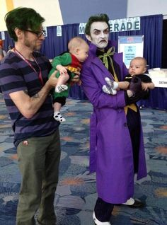 A serious Joker cosplayer holding a baby Batman and Robin.