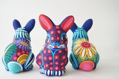 Bunnies in Bloom    These stunning bunnies are made of pottery and then hand painted with an incredible detail and bright colors by artist Laura Helena. A great statement piece to add to your collection.