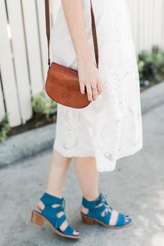 a white embroidered midi skirt with blue sandals