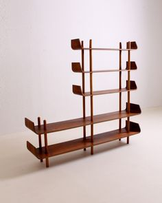 1953 Bookcase or room divider by Willem Lutjens for Gouda den Boer.  Very attractive teak veneered plywood bookcase designed by Willem Lutjens in 1953. During the fifties and sixties a of similar book cases were produced, using the same modular system sticks and shelves combination. Only the Lutjens has the typical bentwood ends on the shelves.