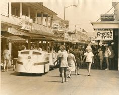 Vintage-Ocean City, Maryland-The Boardwalk Train headed south at the very congested part of the boardwalk at Worcester Street. Businesses in view include; Thrasher's French Fries, Dollie's Candy, The Alaska Stand and Pier Ballroom. Circa 1970.
