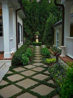 Narrow space is enlarged by: Diagonal pavers narrowing pathway Taller plants next to buildings Focal point at path end Solid greenery backdrop