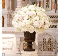 Two lush, all-white floral arrangements in pedestal vases marked the altar.....ceremony flowers