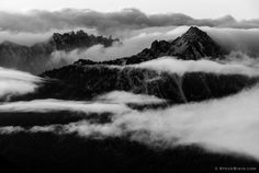 A black and white photograph of mountain ranges surrounding Mount Rainier peaking through the clouds on an Autumn day. Mount Rainier National Park, Washington. | Click the picture above for information on purchasing a fine art photography wall print. | #blackandwhite #landscape #mountains