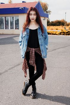 Oversized jean jacket with a plaid shirt tied around the waist along with doc martin boots