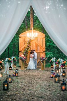 Outdoor woodland ceremony with giant barn door altar and lanterns and florals lining the aisle