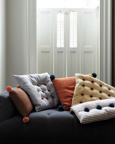 Pom-poms can replace the buttons on tufted pillows, or tassels at the corners of basic square cushions. This works for either store-bought pillows or homemade ones.