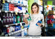 Young female shopper searching for mouthwashes in supermarket