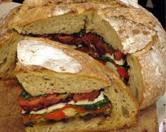 """Pain bagnat"" - so yummy, hollow out some good crusty bread then layer with thinly sliced roasted veggies, mozzarella, and pesto."