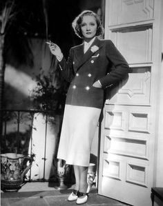 For resort wear milady might well follow the suit of Marlene Dietrich as she appears here from a scene in Desire. Of blue linen, the double-breasted jacket with white pearl buttons tops a short white skirt with an inverted pleat in the center of the front. Marlene's shoes are white with a wide, crushed strap of blue kid across the instep.