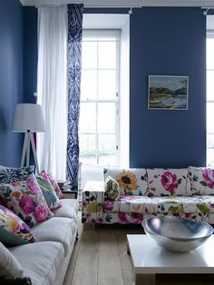Blue walls, floral print sofa and pillows bring  nature into your home.