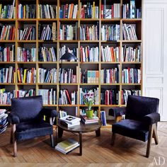 Custom-made bookshelves span a wall in the study of decorative-arts dealers Laurence and Patrick Seguin's Paris home. The floor lamp is by Serge Mouille.