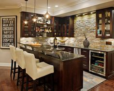 Natural stone backsplash, clear view cabinets, cream bar chairs, granite countertops, wine fridge, pendant lighting | Creative Design Construction, Inc.