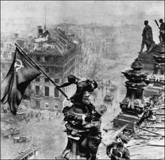 Reichstag flag [1945]    Soviet Union soldiers Raqymzhan Qoshqarbaev and Georgij Bulatov raising the flag on the roof of Reichstag building in Berlin, Germany in May, 1945.