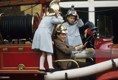 Prince William and Prince Harry (R) play on top of a fire engine on March 1, 1988 in Sandringham, England.