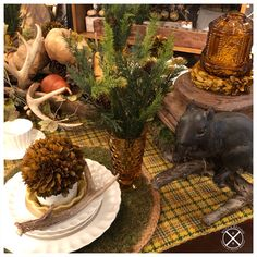Autumn fall tablescape. Vintage amber glassware, vintage picnic throw as a base, vintage Spode dishes based with jute and moss placemats, antlers, boxwood and evergreen to introduce Christmas and Winter for the Thanksgiving Table. Also used gourds and antlers and pinecones to fill the centerpiece doughbowl, and flanked that with vintage column bases topped with amber fairy light candles. Whimsical squirrel adds to the mix. Autumn Fall, Winter, Column Base, Vintage Picnic, Centerpieces, Table Decorations, American Decor, Thanksgiving Table, Gourds
