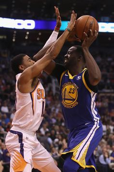 Draymond Green of the Golden State Warriors drives the ball against Shaquille Harrison of the Phoenix Suns during the first half of the NBA game at...