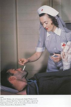 Volunteer Red Cross Nurse and wife of a USN officer lights a cigarette for a military patient.
