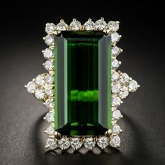 Measuring a striking and impressive 1 1/8 inch long, this enchanting showstopper features a rich deep green elongated emerald-cut Tourmaline weighing in at 14.51 carats. The entrancing gemstone radiates from within a sparkling frame composed of small round brilliant-cut diamonds, with trios of the same enlivening each shoulder. A jubilant estate jewel rendered in rich 18K yellow gold. 1.40 carats total diamond weight. Currently ring size 5 1/4 +.