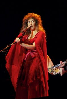 Steve, rocking it in red onstage singing some song that has her looking sideways; the stage lights make her hair look red too   ~ ☆♥❤♥☆ ~