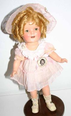 """13"""" compo Shirley Temple doll from around 1936, notice the high cheek color, golden hair and thick distinct curl set. Shirley is wearing a very rare dress, it has been identified as being from Dimples (in the scene wearing she is playing Eva in Uncle Tom's Cabin) but I'm not sure if this is correct, as this one is tagged with the NRA tag which only was available (around) March 1935 Z"""