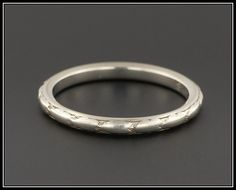 A lovely vintage 18k white gold wedding band from the late Art Deco era. This ring is marked 18k and bears the mark for the Traub company. The interior of the band is engraved N.M - J.H. 4-3-29 presumably commemorating a wedding date.   This ring is a size 5 and cannot be re-sized with out a bit of loss to the detail on the outside of the band. We have many other fantastic offerings of period fine and costume jewelry posted on our Etsy store, so please consider browsing our other items. We…