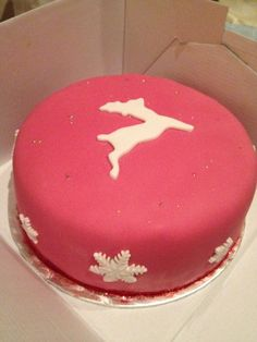 Christmas cake in pink and white with reindeer and snowflake decoration.